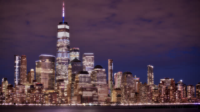 illuminated financial and business buildings at night. beautiful colorful new york skyline at nighttime. waterfront. one world trade center and other famous places. travel destination. - panoramic stock videos & royalty-free footage