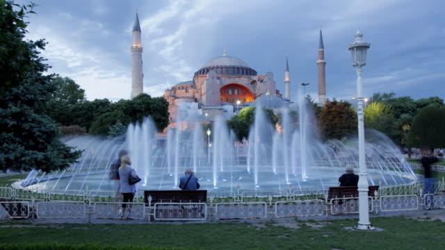 stockvideo's en b-roll-footage met t/l ws illuminated fountain in sultanahmet park, hagia sophia in background, dusk / istanbul, turkey - rond de 15e eeuw