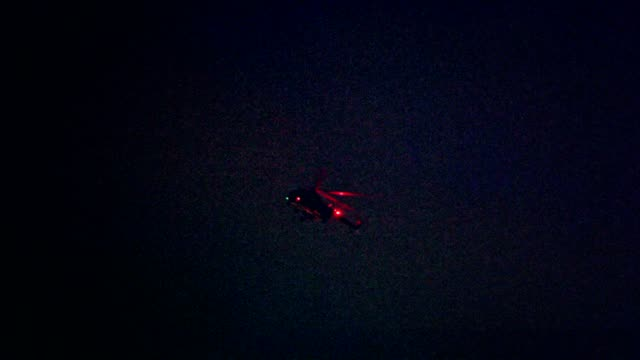 illuminated helicopter flying above city in night - helicopter stock videos and b-roll footage