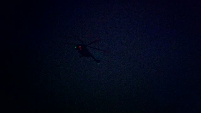 illuminated helicopter flying above city in the night - low angle view stock videos & royalty-free footage