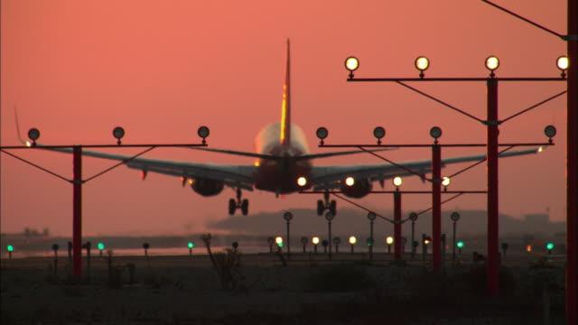 vídeos de stock e filmes b-roll de ms, illuminated landing lights and airplane landing on runway against orange sky at sunset, rear view, los angeles, california, usa - aeroporto internacional de los angeles