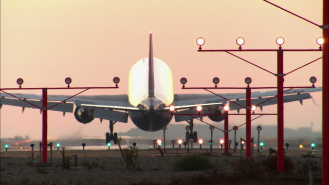 MS, Illuminated landing lights and airplane landing on runway against orange sky at sunset, rear view, Los Angeles, California, USA