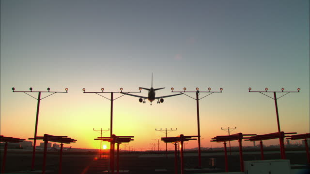 stockvideo's en b-roll-footage met ws, illuminated landing lights and airplane landing on runway at sunset, rear view, los angeles, california, usa - lax airport
