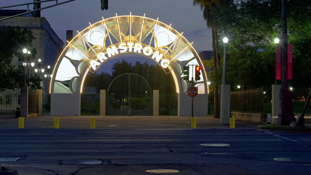 WS T/L ZO Illuminated Louis Armstrong Park entrance with traffic on road at dusk / New Orleans, Louisiana, USA