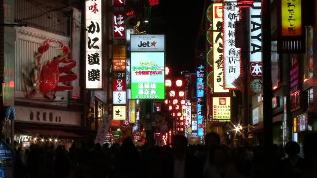 ms, illuminated neon above crowded dotonbori street at night, osaka, japan - lanterna attrezzatura per illuminazione video stock e b–roll