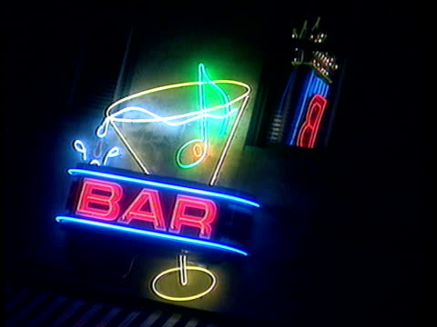 Illuminated neon sign with moving cocktail glass on Beale Street at night