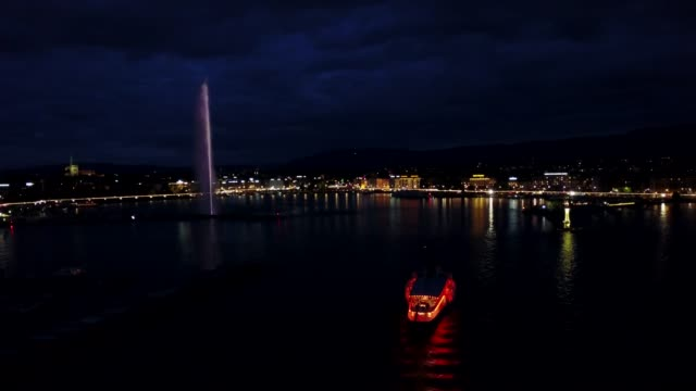 vidéos et rushes de illuminated night view over jet d'eau fountain in geneva, switzerland - fontaine