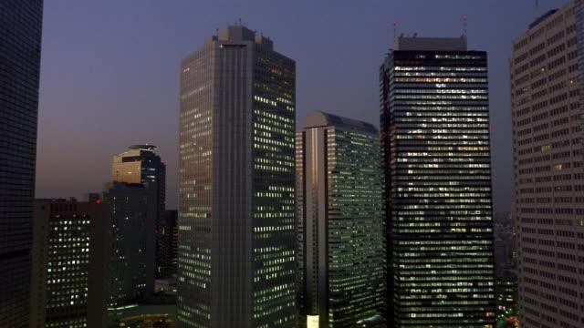 fast motion, ms, illuminated office buildings at night, tokyo, japan - fönsterrad bildbanksvideor och videomaterial från bakom kulisserna
