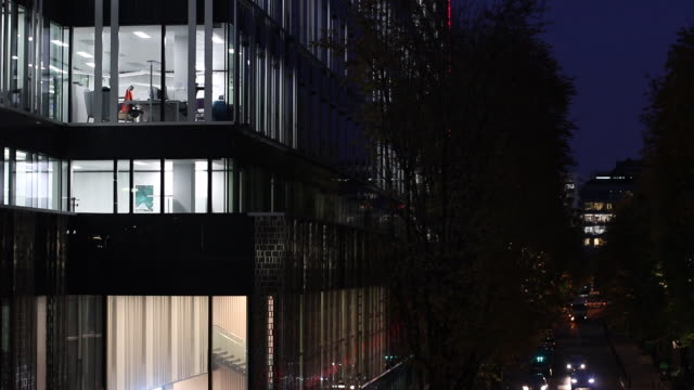 illuminated offices through glass windows at night - working overtime stock videos & royalty-free footage