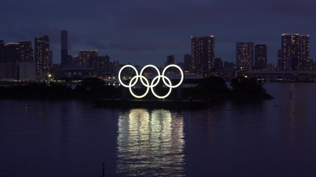 illuminated olympic rings are seen in front of buildings at night on the day marking one year to go until the tokyo olympic games on july 23, 2020 in... - tokyo japan stock videos & royalty-free footage