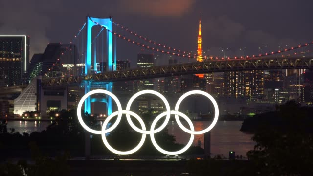 illuminated olympic rings are seen in front of the rainbow bridge and the tokyo tower at night on the day marking one year to go until the tokyo... - tokyo japan stock videos & royalty-free footage