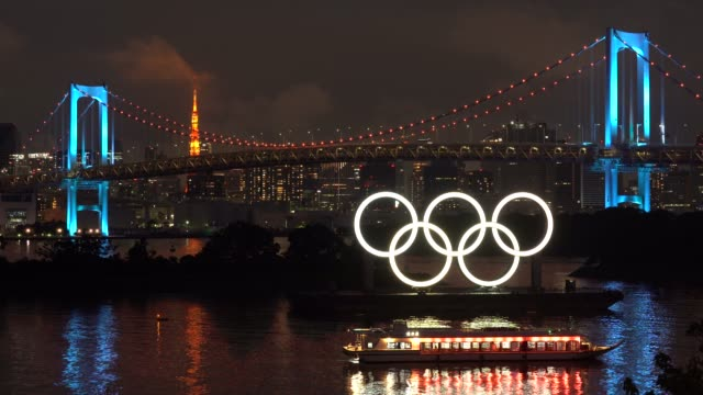 illuminated olympic rings are seen in front of the rainbow bridge and the tokyo tower at night on the day marking one year to go until the tokyo... - minato ward stock videos & royalty-free footage
