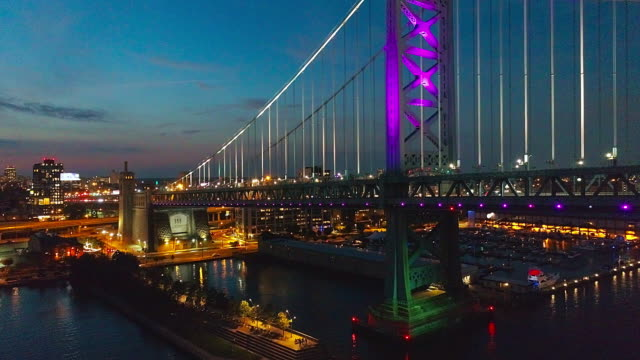 vídeos de stock e filmes b-roll de illuminated philadelphia downtown, benjamin franklin bridge and piers in old city at delaware river at night. aerial drone video with the slow forward camera motion. - ponte ben franklin
