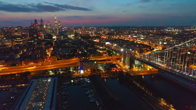 vídeos de stock e filmes b-roll de illuminated philadelphia downtown, benjamin franklin bridge and piers in old city at delaware river at night. aerial drone video with the static camera. - ponte ben franklin