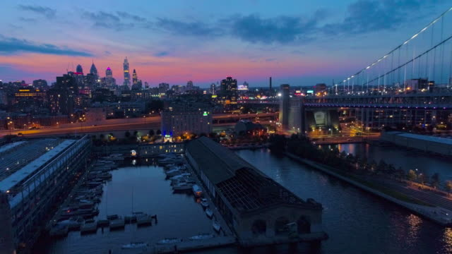 vídeos de stock e filmes b-roll de illuminated philadelphia downtown, benjamin franklin bridge and piers in old city at delaware river at night. aerial drone video with the backward camera motion. - ponte ben franklin