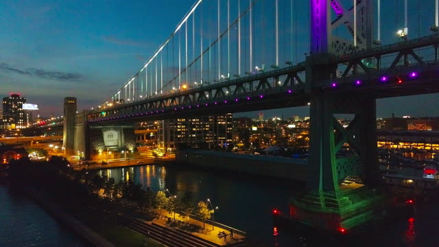 vídeos de stock e filmes b-roll de illuminated philadelphia downtown, benjamin franklin bridge and piers in old city at delaware river at night. aerial drone video with the descending camera motion. - ponte ben franklin