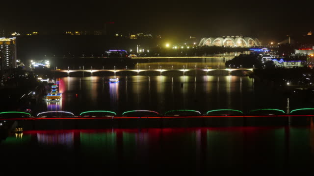 tl – illuminated riverboat cruising at night on taedong river in pyongyang, north korea, dprk. wide shot from above - spoonfilm stock videos and b-roll footage