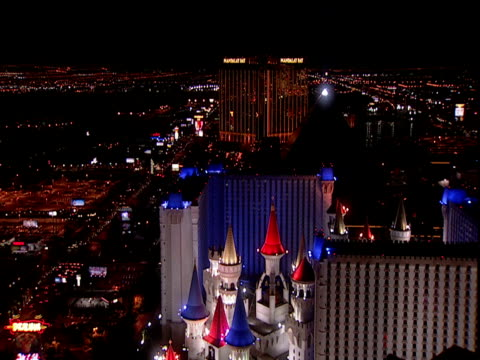 illuminated rooftops of theme hotels and city lights into distance at night las vegas - casino stock videos & royalty-free footage