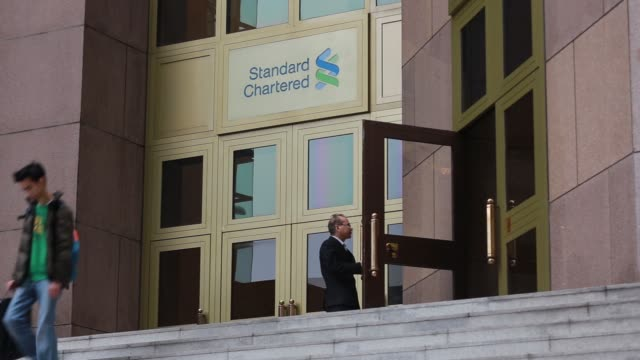 illuminated signage for standard chartered plc bank logo is displayed inside a branch in hong kong, as customers walk past, signage for standard... - branch stock videos & royalty-free footage