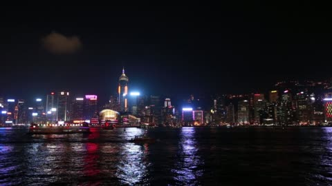 illuminated skyline of hong kong island as a ferry sails along victoria harbor on a clear night - hong kong island stock videos & royalty-free footage