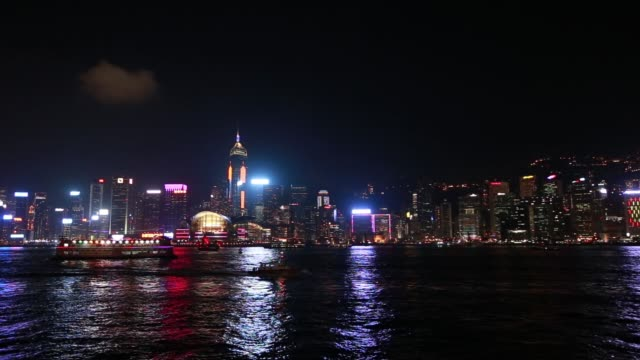 stockvideo's en b-roll-footage met ws illuminated skyline of hong kong island as a ferry sails along victoria harbor on a clear night - hongkong eiland