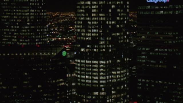 aerial illuminated skyscrapers downtown at night / los angeles, california, united states - breitwandformat stock-videos und b-roll-filmmaterial