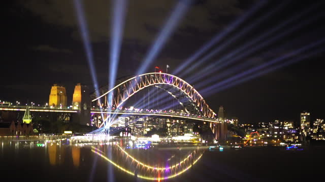 illuminated sydney harbor bridge with light beam and reflection - traditional festival stock videos & royalty-free footage