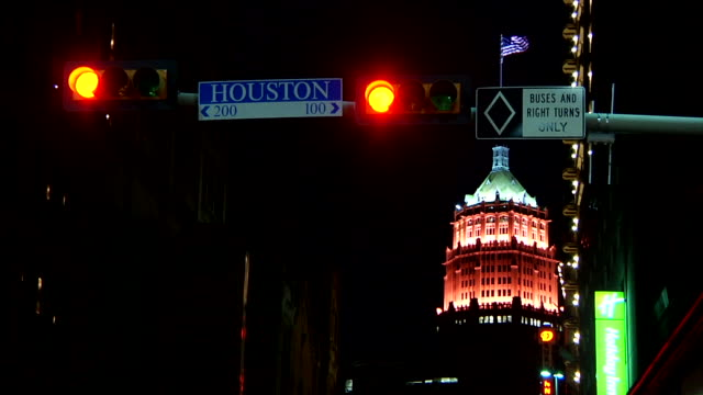 stockvideo's en b-roll-footage met illuminated tower life building w/ waving american flag atop building in bg and 'houston' street sign, traffic sign & red lights on pole in fg - b roll