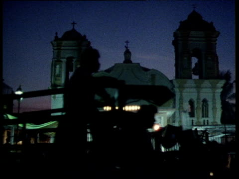 Illuminated train station silhouetted vehicles drive in foreground Mexico
