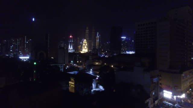 vídeos de stock, filmes e b-roll de illuminated urban skyline of kuala lumpur, malaysia by night - torre menara kuala lumpur