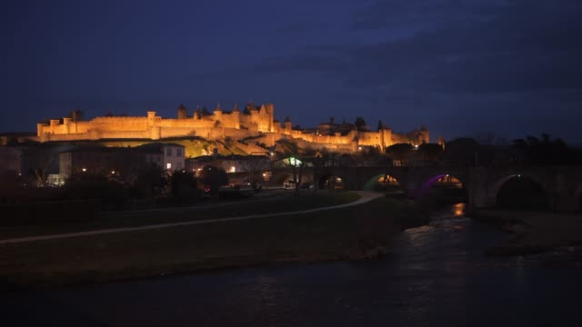 illuminated walls of historic carcassonne with river aude, languedoc - roussillon, france. unesco world heritage site. - aude stock videos & royalty-free footage