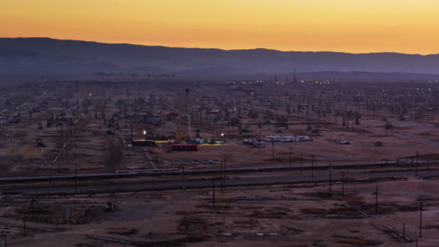 Illuminated Work Site in South Belridge Oil Field in Kern County, California at Dusk - Drone Shot