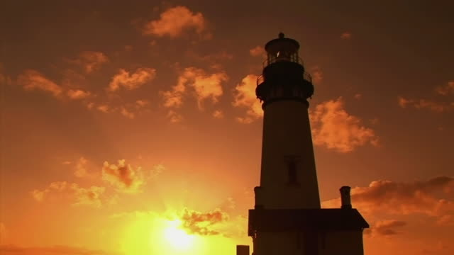 ms la illuminated yaquina head lighthouse against sky at sunset / newport, oregon, usa - yaquina bay lighthouse stock videos & royalty-free footage