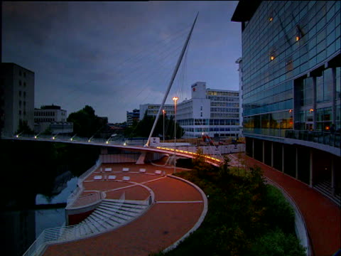 illuminations turn on as night falls over trinity footbridge manchester - manchester stock videos and b-roll footage