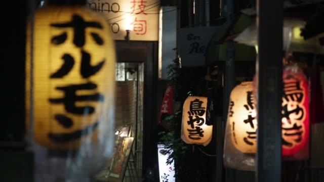 Illumined lanterns hang outside the entrance of a restaurant in Tokyo Japan on Thursday Dec 11 Pedestrians walk past illuminated lanterns hanging...