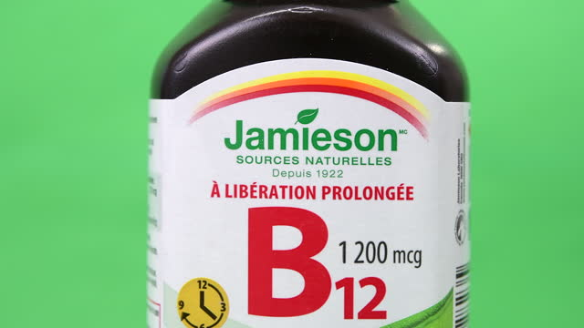 illustrative editorial clip of a jamieson branded bottle of vitamin b12 seen on march 18, 2021 in toronto, ontario, canada. studio shot with a green... - coloured background stock videos & royalty-free footage