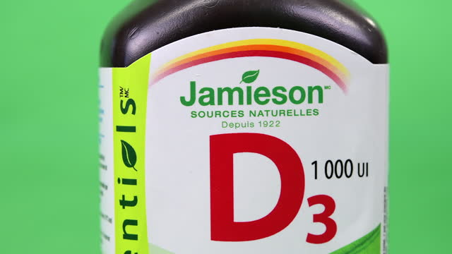 illustrative editorial clip of a plastic container of jamieson branded vitamin d3 seen on march 18, 2021 in toronto, ontario, canada. studio shot... - coloured background stock videos & royalty-free footage