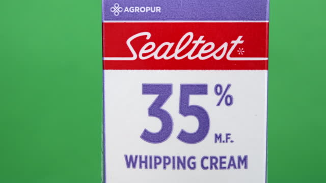 illustrative editorial clip of whipping cream branded sealtest by agropur on march 18, 2021 in toronto, ontario, canada. studio shot with a green... - coloured background stock videos & royalty-free footage