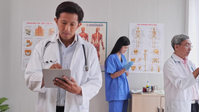 image of a doctor working inside the examination room by using the tablet x-ray film and medical devices - medical examination room stock videos & royalty-free footage