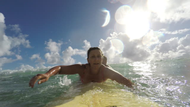 pov image of middle aged woman surfing at the beach - surfboard stock videos and b-roll footage