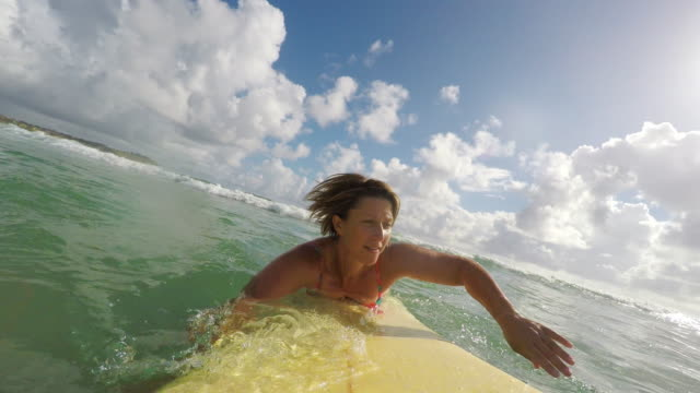 pov image of middle aged woman surfing at the beach - pagaiare video stock e b–roll