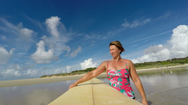 pov image of middle aged woman surfing at the beach - body positive stock videos & royalty-free footage