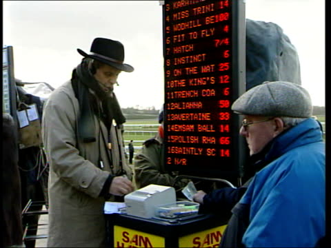 stockvideo's en b-roll-footage met image tarnished itv evening news penny marshall itn england lingfield ext horses out of gates along at start of race pan bookmaker shouting odds sot... - john mccririck
