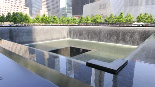 images of nearby buildings reflect in water at a 9/11 memorial recessed pool. - memorial stock videos and b-roll footage