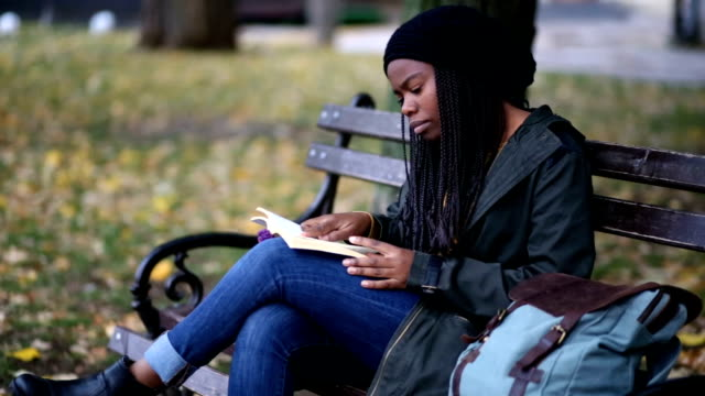 imaginative woman reading on park bench - park bench stock videos & royalty-free footage