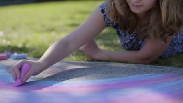 cu imaginative young girl sketches colorful rainbow with sidewalk chalk - symbols of peace stock videos & royalty-free footage