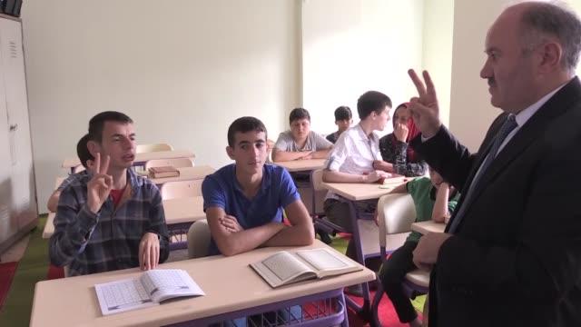 vídeos y material grabado en eventos de stock de imam cemal elcioglu gives religious education to 13 children including 4 hearingimpaired children and 8 autistic children at kizilcikdibi mosque in... - hacer señas