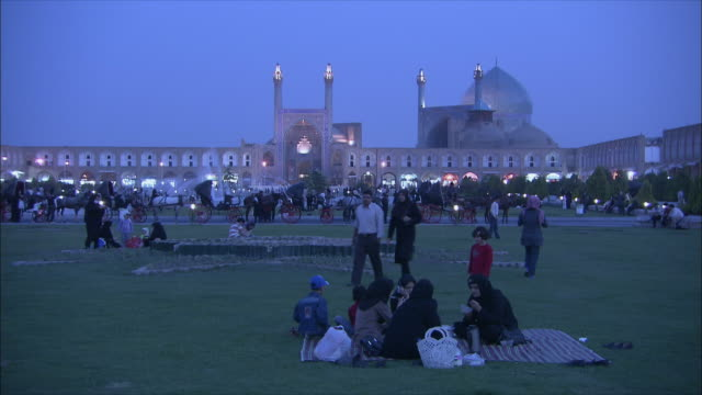 WS Imam Khomeini Mosque and Sheikh Lotfollah Mosque illuminated at dusk, people having picnic on lawn in foreground, Naghsh-e Jahan Square, Isfahan, Iran