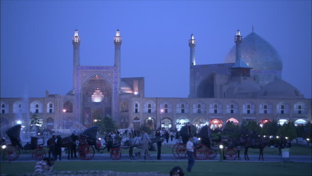 WS Imam Khomeini Mosque and Sheikh Lotfollah Mosque illuminated at dusk, people and horse carts in foreground, Naghsh-e Jahan Square, Isfahan, Iran