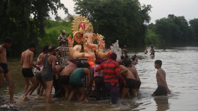 immersed of god ganesha in to the river of village, maharashtra, india. - グジャラート州点の映像素材/bロール
